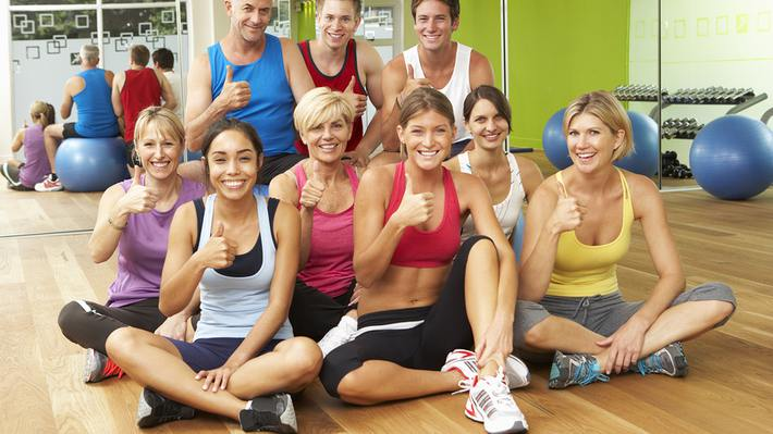 Group of people sitting on a gym floor with thumbs up.